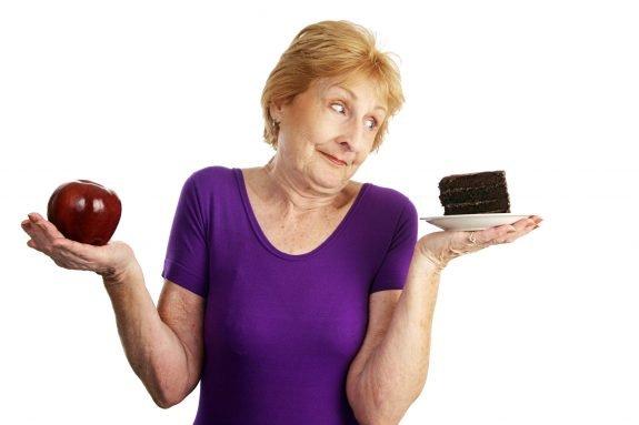 Senioren Dame entscheidet zwischen gesundem Apfel und verführerischem Kuchen - Es geht aber auch lecker & gesund!