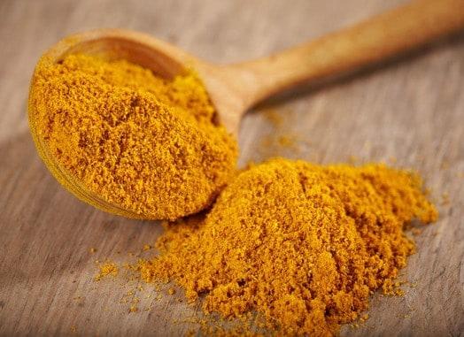 Currypulver auf Löffel und Brett