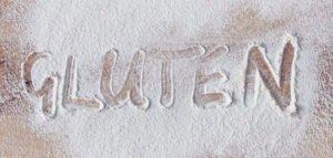 Holzbrett mit Mehl und das Wort Gluten